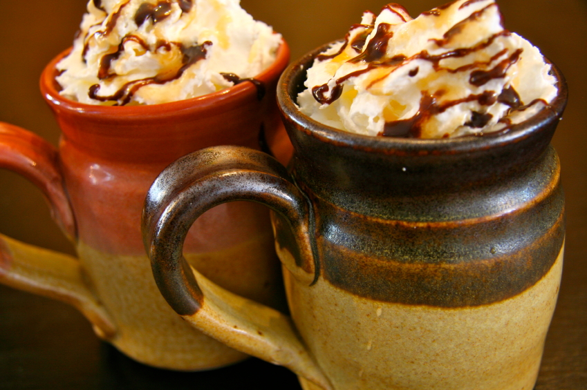 two mugs of hot chocolate with whipped cream drizzled with caramel and chocolate