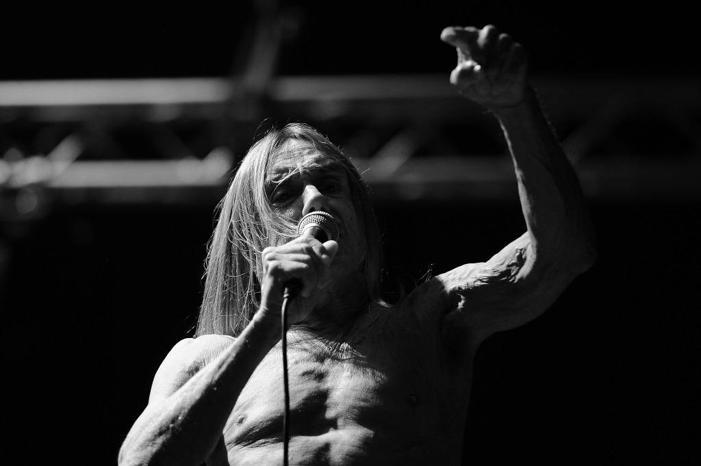 Iggy Pop is shirtless and wearing sunglasses with one hand in the air.