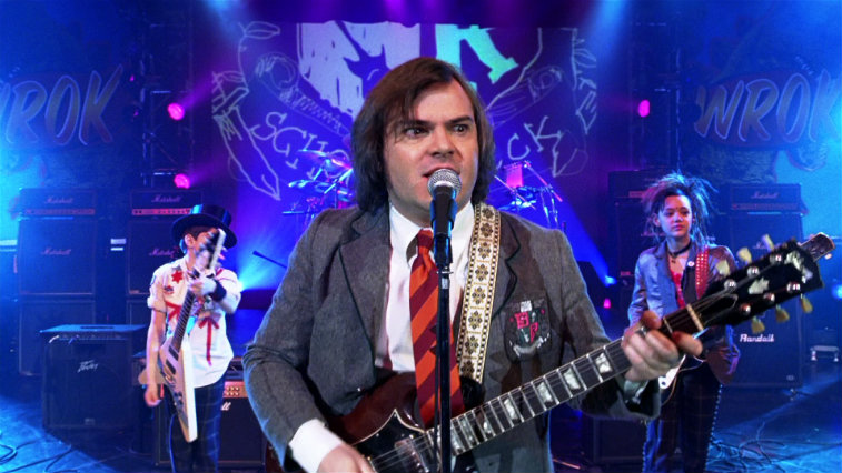 Jack Black wearing a suit, playing a guitar, and singing