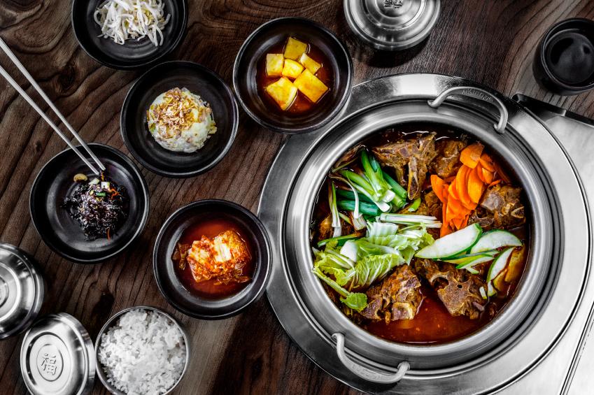 korean hot pot soup with scallions, carrots, an cucumbers