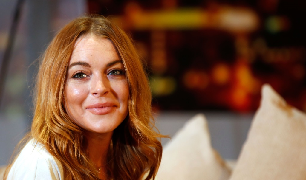 Actress Lindsay Lohan is sitting on a couch and smiling.