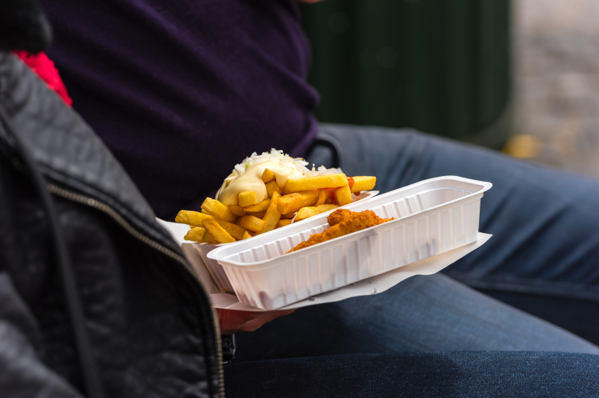 man wearing a purple shirt and jeans eating fries and fried fish out of to-go containers
