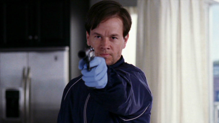 Mark Wahlberg is holding up a gun.