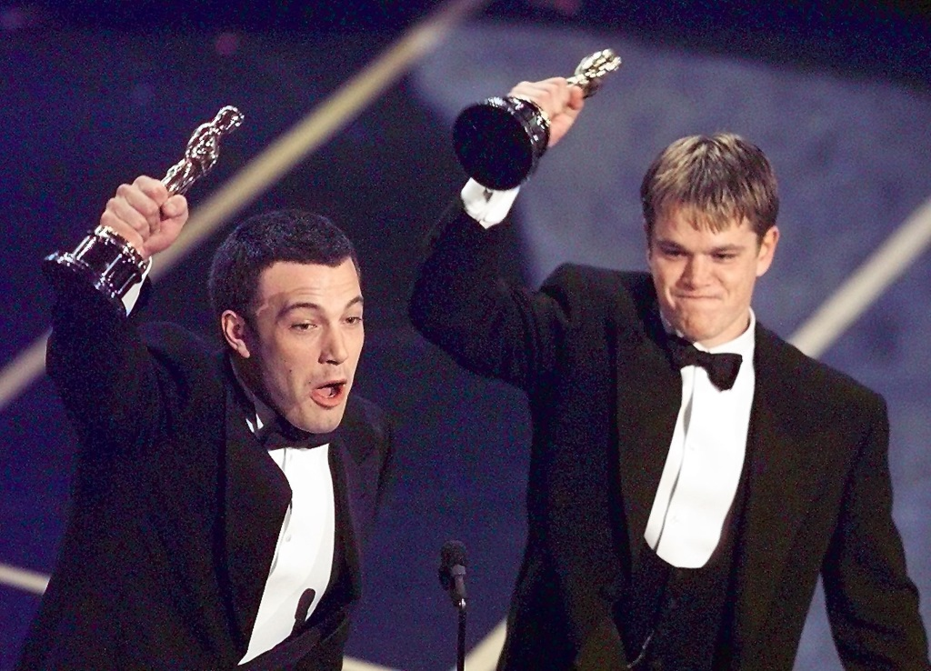 Matt Damon and Ben Affleck at the Oscars holding up their awards.