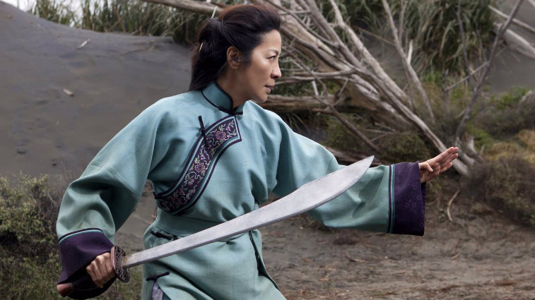 Yu Shu Lien is in a stance holding up one hand and a samurai sword in the other.