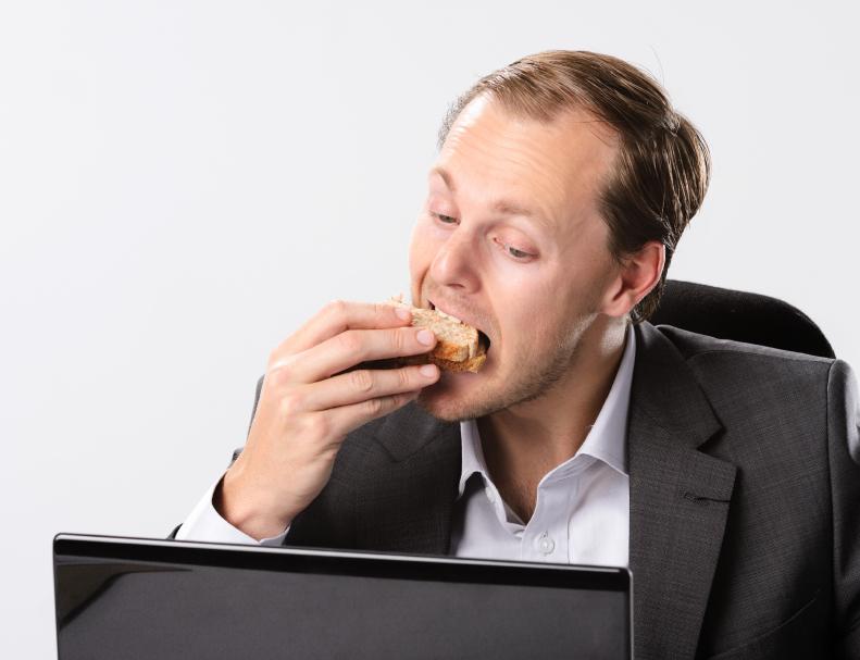 A man scarfs food at his desk
