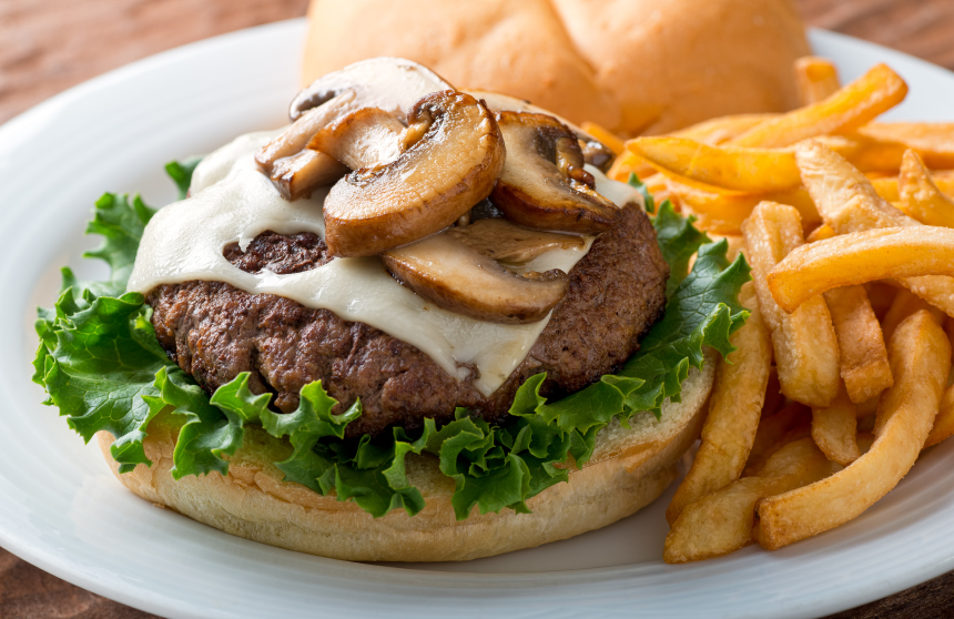 burger with mushrooms and swiss cheese without the top bun and a side of oven fries