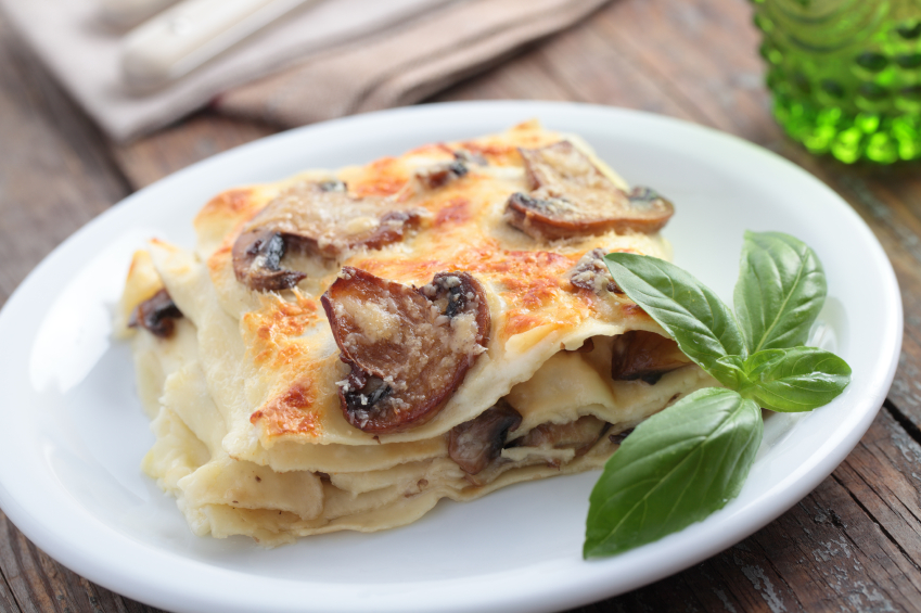white plate with a slice of mushroom and cheese lasagna