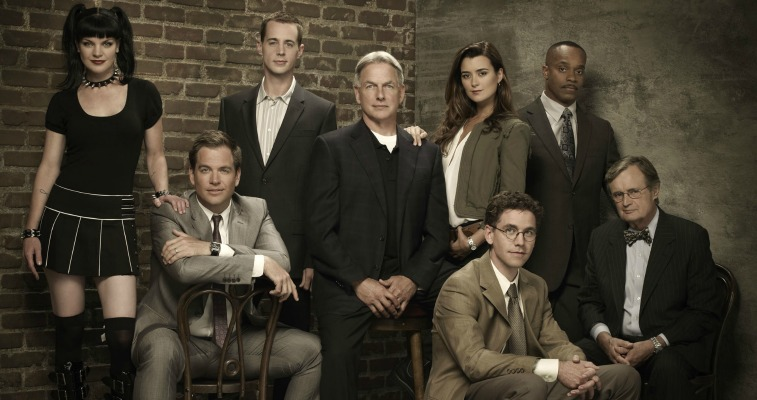 The cast of NCIS poses in front of a brick wall