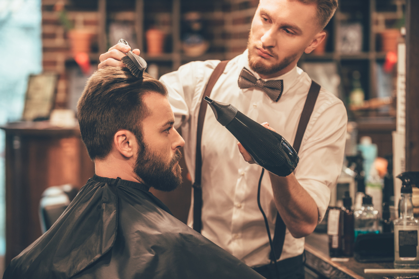 Brunette man getting a haircut from a man wearing a bow-tie and suspenders