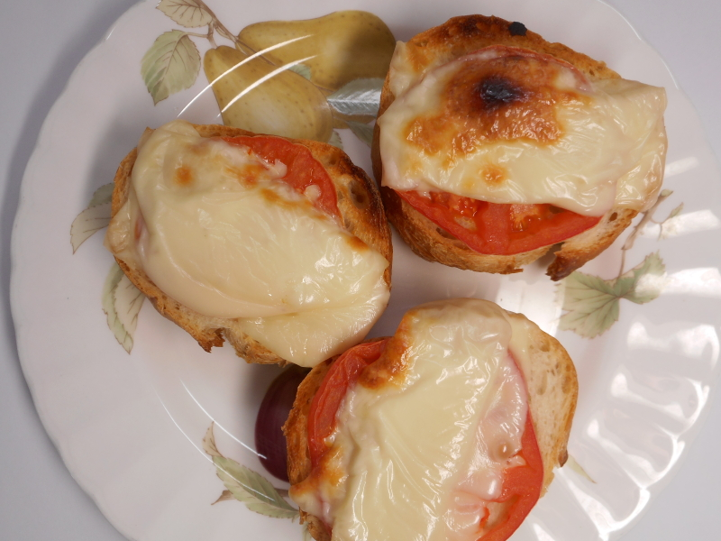 plate of open-face sandwiches with tomatoes and melted cheese on toast