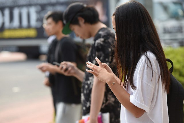 Students standing in a line texting on their smartphones