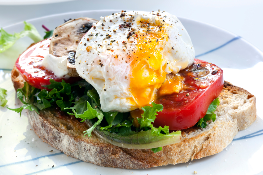 open face sandwich on rustic toast with eggs, tomatoes, and lettuce