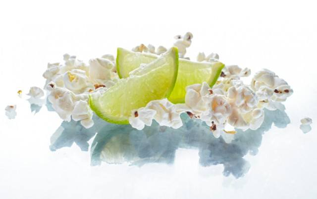 lime popcorn with lime wedges on a white surface