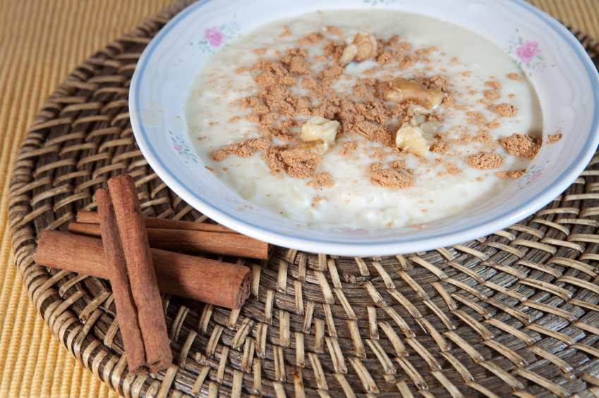 bowl of rice pudding topped with brown sugar, cinnamon, and walnuts