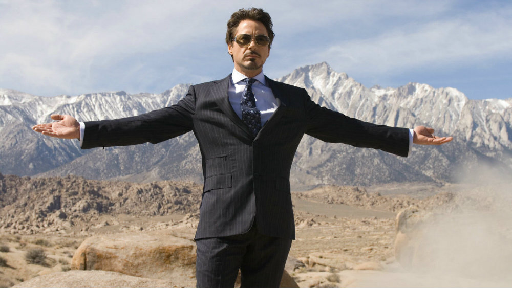 Robert Downey Jr in a suit with his arms reaching out in front of a mountain