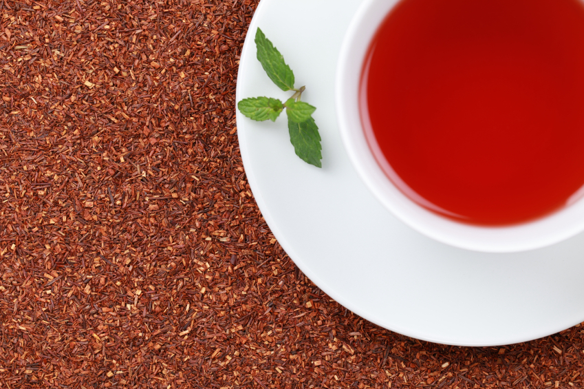 cup of rooibos tea with a sprig of lemon balm