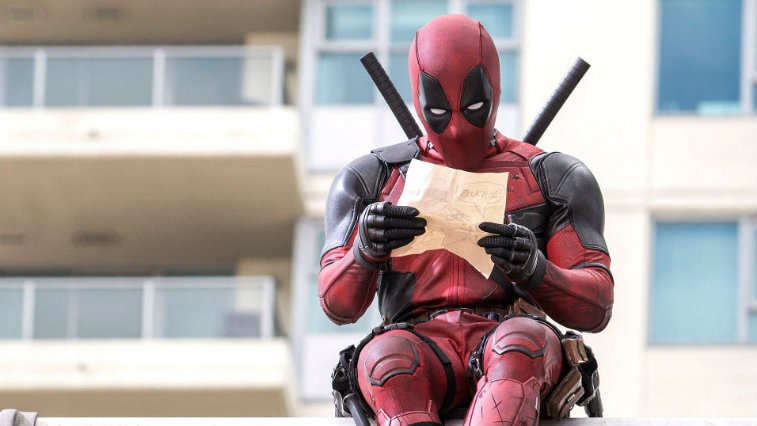 Deadpool sits on a ledge in front of a building and reads a piece of paper