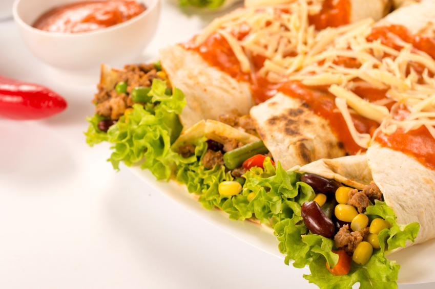Enchiladas with fresh veggies, beans, and corn