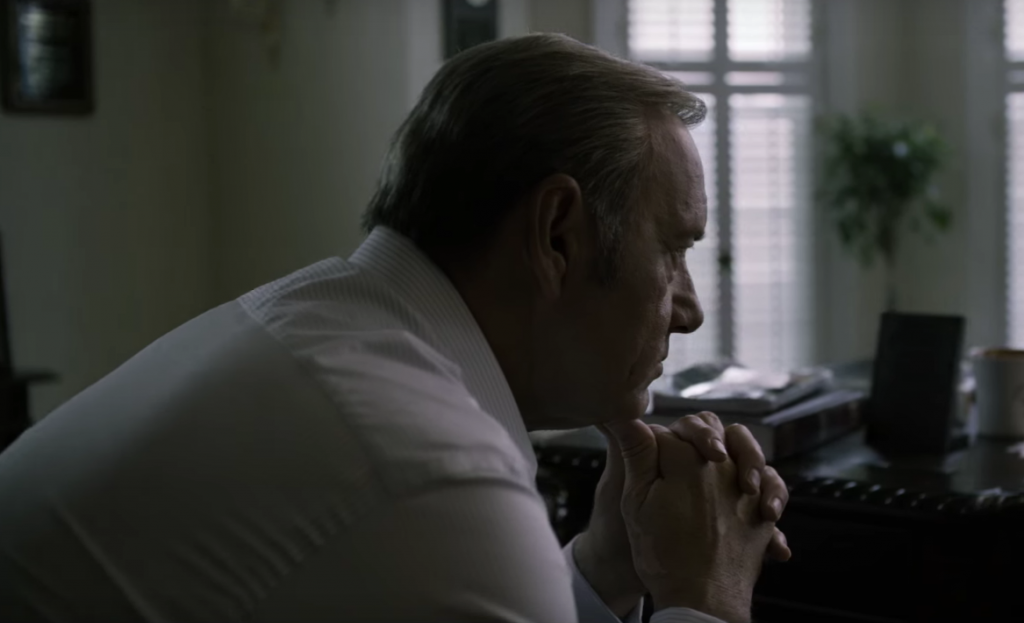 Frank leans his chin in his hands in House of Cards
