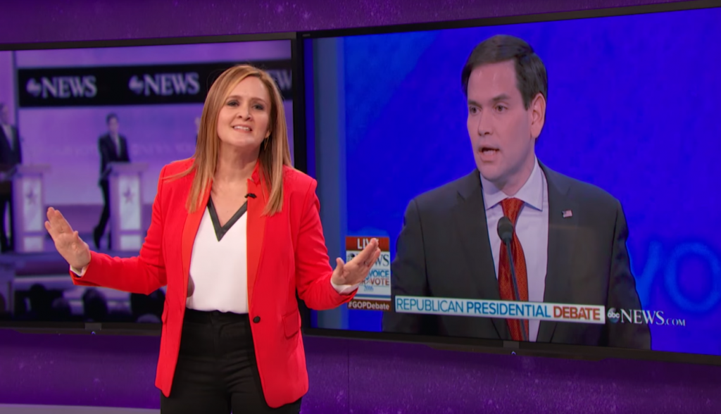 Samantha Bee stands in front of a TV screen