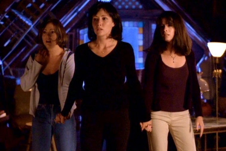 Alyssa Milano, Shannen Doherty, and Holly Marie Combs as the Halliwell sisters standing together in an attic on Charmed