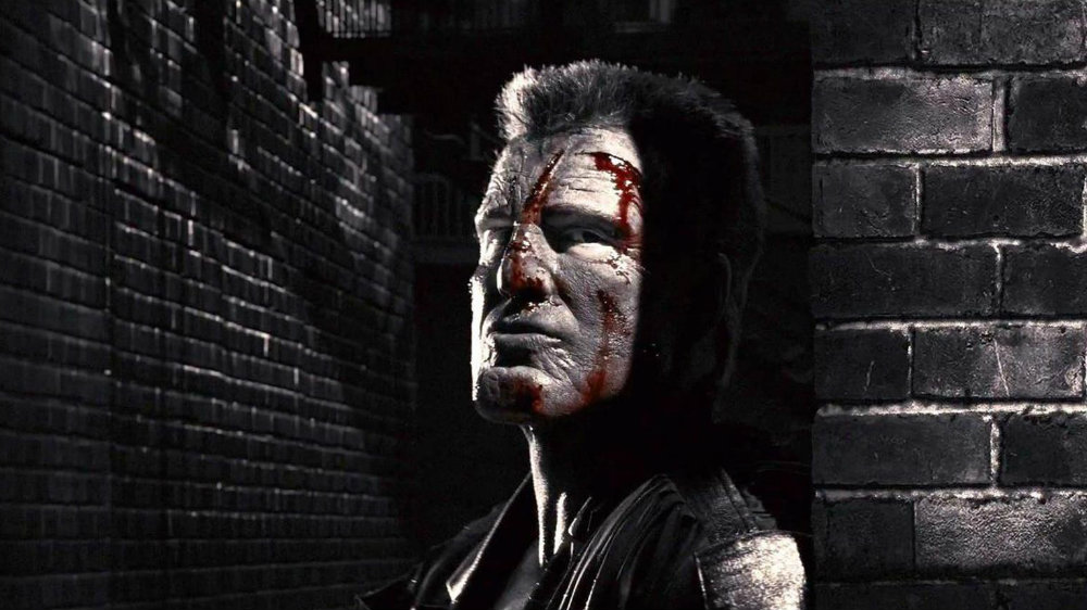 A bloodied Mickey Rourke in Sin City, cloaked in shadows and looking to his left