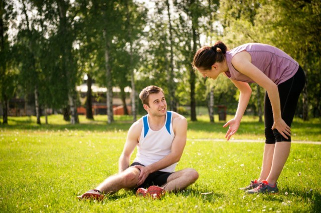 runner sitting in the grass holding a leg injury