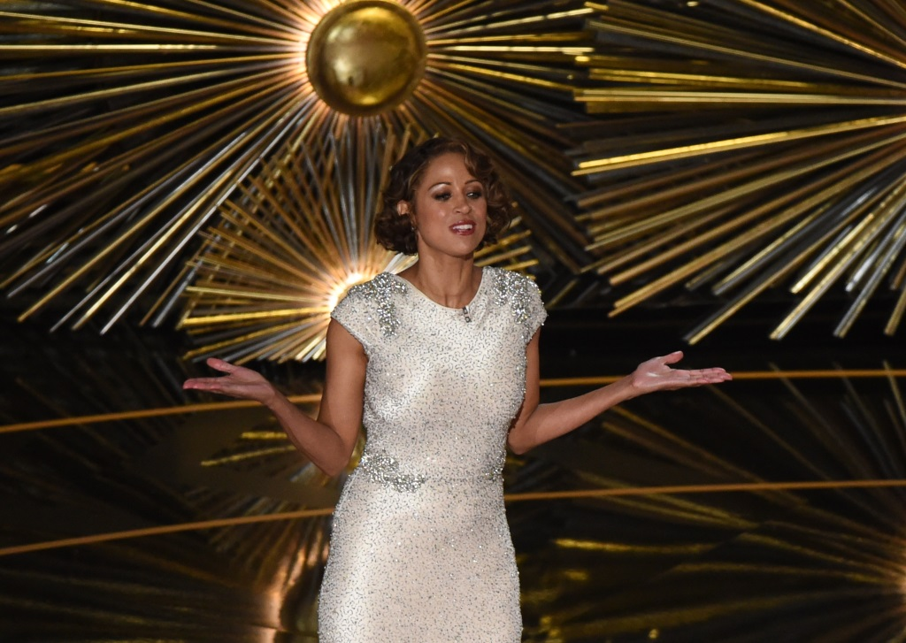 Stacey Dash is on stage at the Academy Award in a white dress with her arms out.