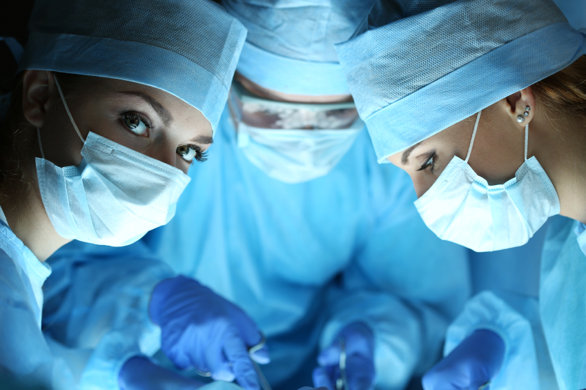 three surgeons operating in a surgical theatre