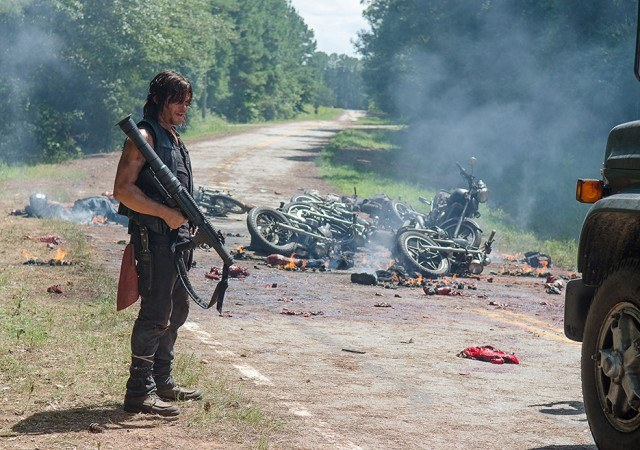 Daryl with a rocket launcher standing on the road after a massive motorcycle collision