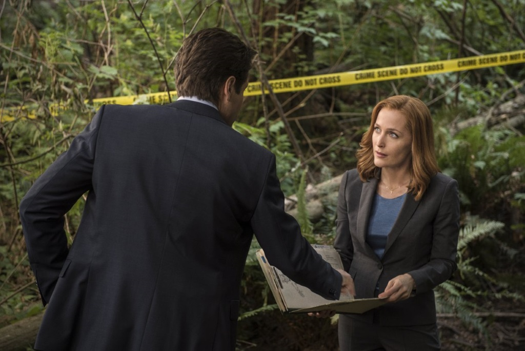 Gillian Anderson looks up at David Duchovny while standing in front of a crime scene with yellow police tape