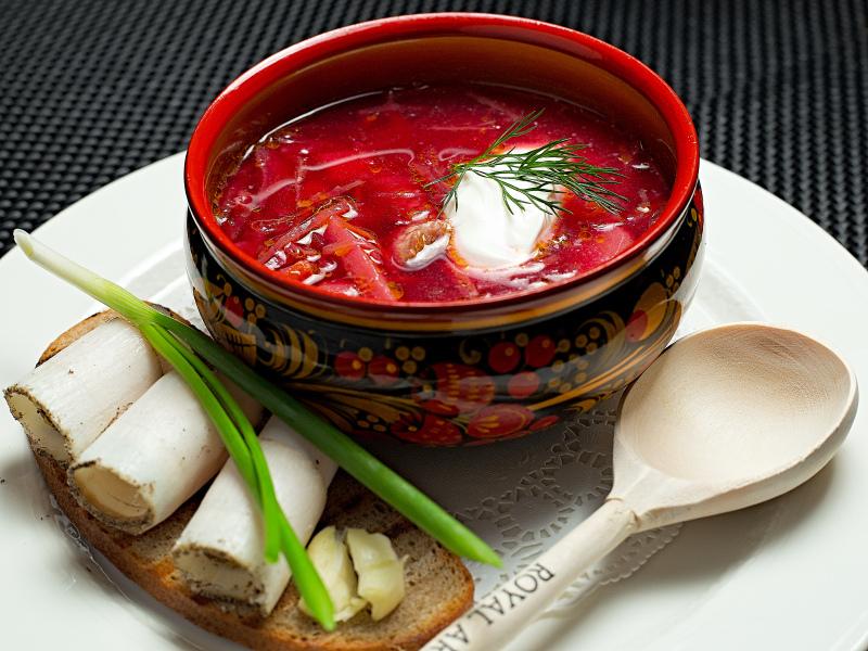 bowl of beet borscht with dill, sour cream and a side of buttered bread