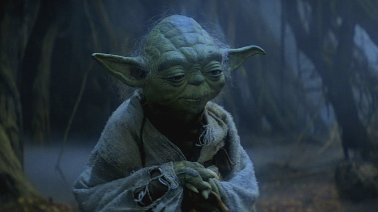 Yoda looks down while wearing a frayed shawl