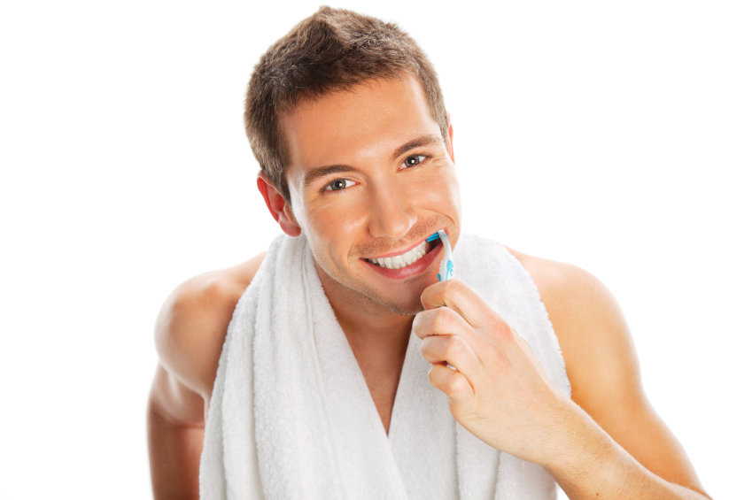 A man whitening his teeth