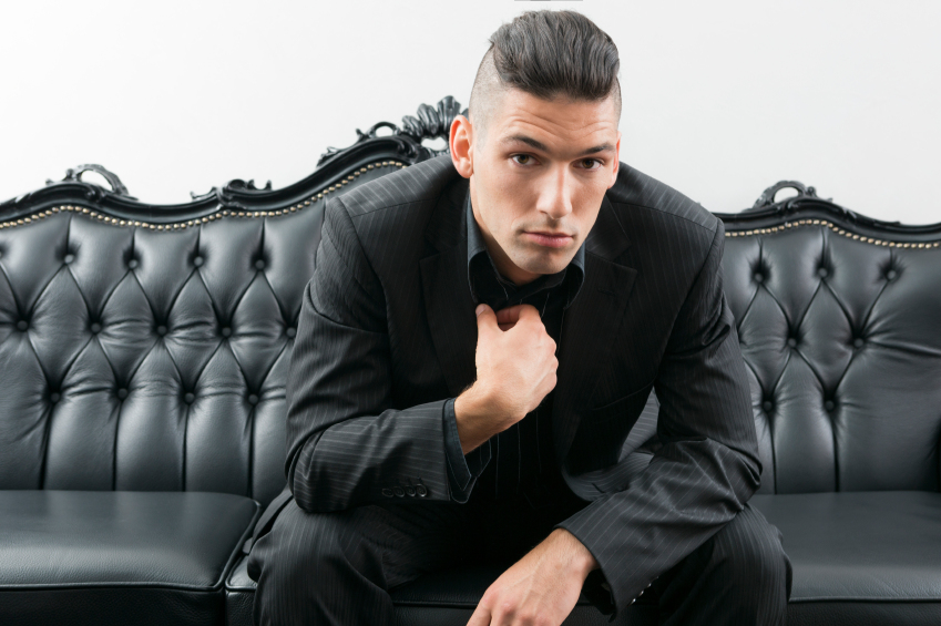 young man wearing black suit sitting on sofa