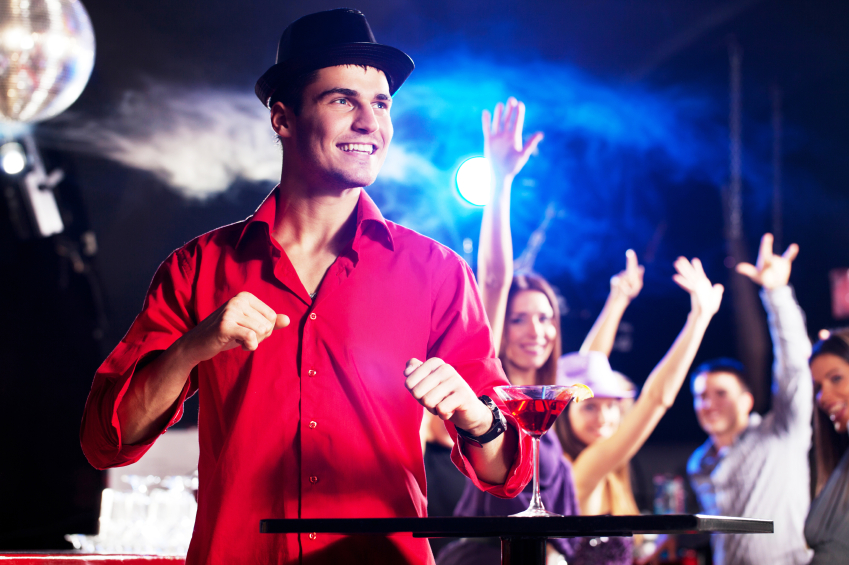 young man dancing in a club wearing red shirt