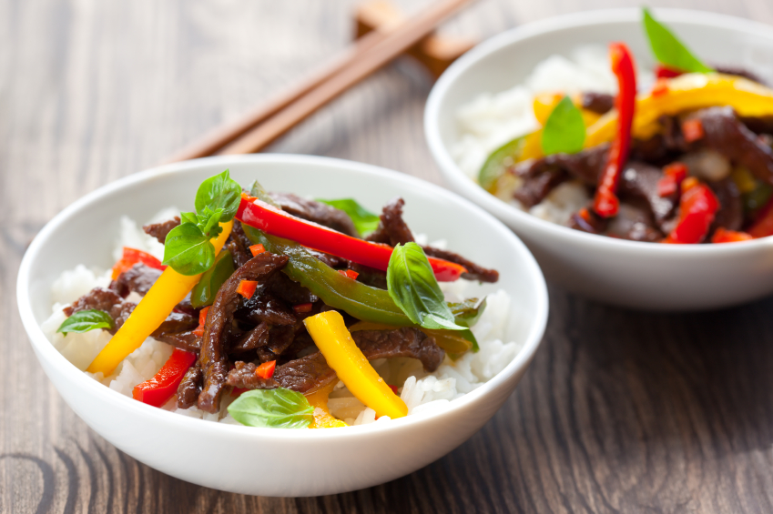 beef and pepper stir fry in white bowls with rice