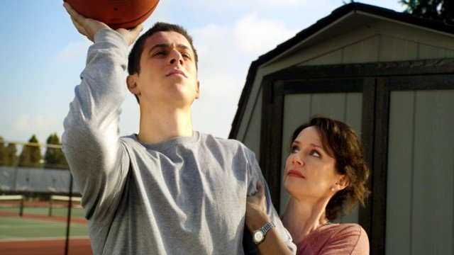 Man throwing basketball and woman holding onto him