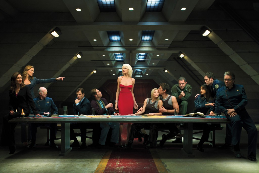 The cast of Battlestar Galactica stand around a conference table