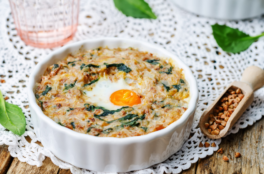 baked casserole with buckwheat, spinach, cheese, and an egg in a white ramekin