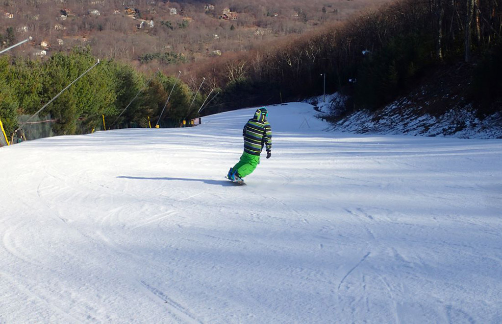 snowboarder gliding down mountain at Camelback Mountain Resort in Tannersville, Pennsylvania