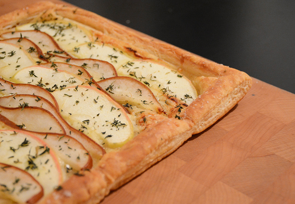 cheddar, apple, and pear tart on a wooden cutting board