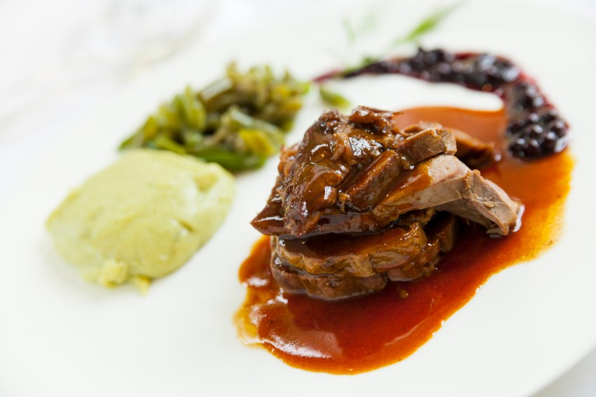 gourmet venison dish with sauce, potatoes, and green vegetables