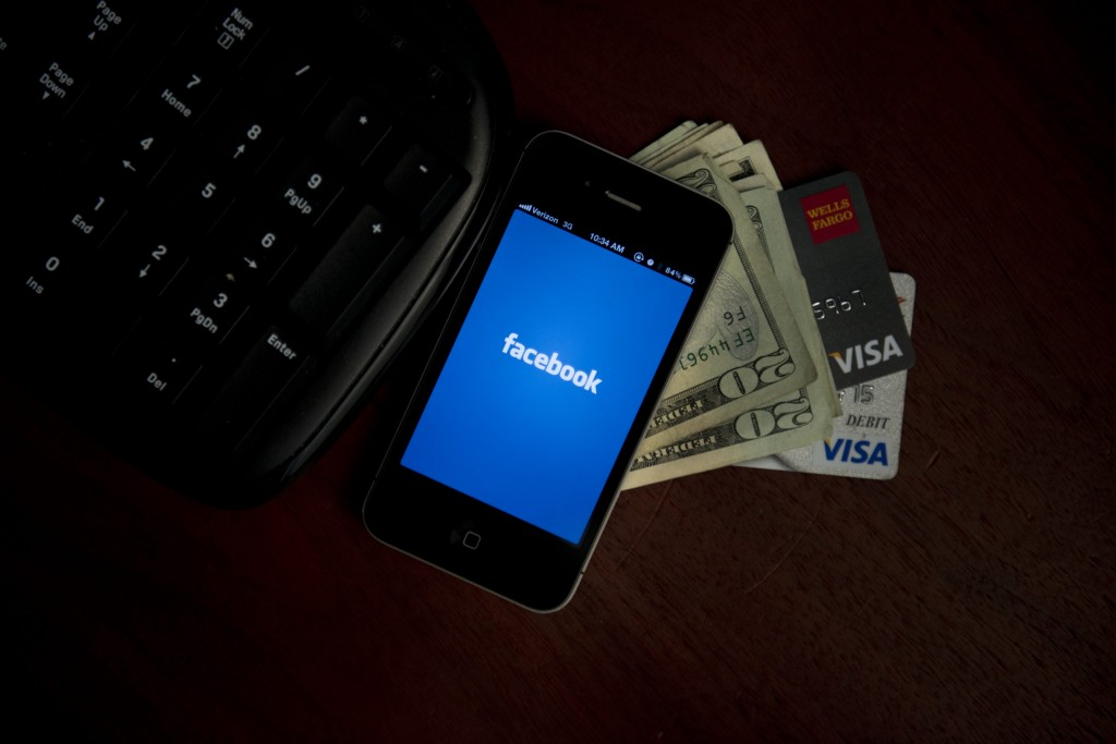 facebook on phone with cash and credit cards
