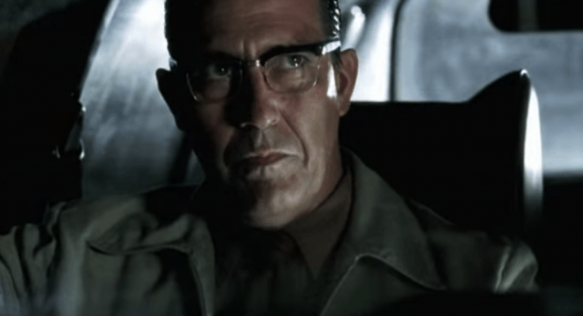 Ciaran Hinds wears glasses and looks up while sitting in a car