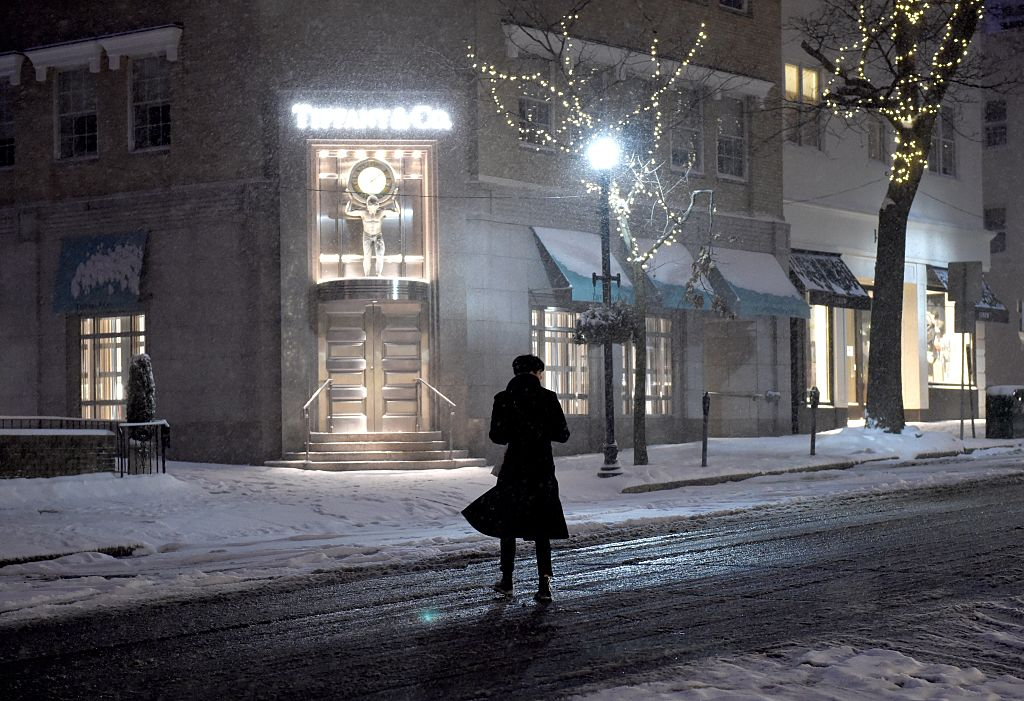 A woman crosses a snowy street in Connecticut.