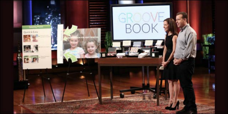 Julie and Brian Whiteman are in front of pictures and examples of Groovebook on Shark Tank.