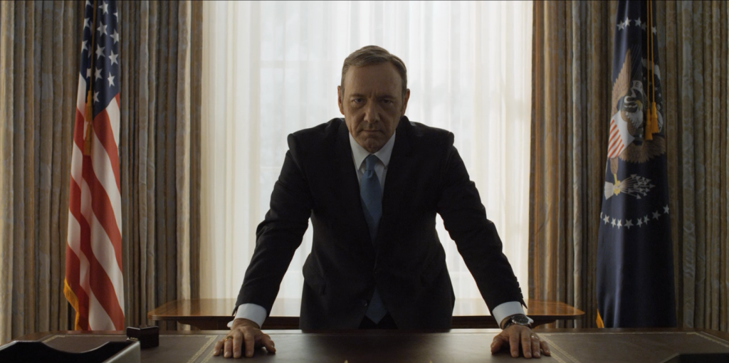 Frank Underwood leaning over the desk in the Oval Office, looking directly at the camera