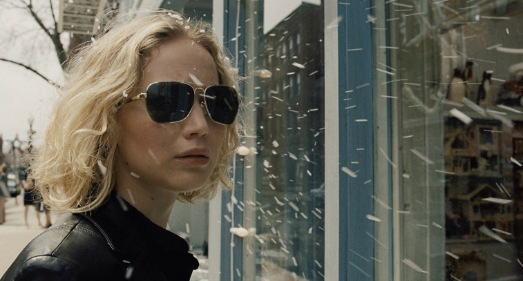 Jennifer Lawrence wears sunglasses and stands outside a store window in Joy